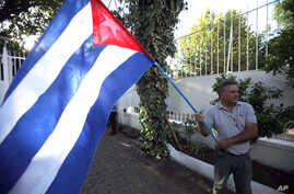 A man waves a Cuban flag while celebrating the restoration of diplomatic relations between Havana and Washington, in the courtyard of the Cuban Embassy in Santiago, Chile, Dec. 17, 2014.