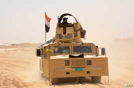 Iraqi government forces drive their armored vehicle, June 22, 2016, some 40 kilometers (25 miles) west of Qayyarah, during their operation to take the city and make it a launchpad for Mosul.