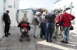 A police officer (L) stands guard as tourists walk in Sidi Bou Said, a tourist destination, in Tunis March 23, 2015. Tunisian Prime Minister Habib Essid fired six police commanders on Monday, including the head of tourist security, after a militant a...