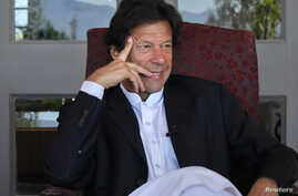 Imran Khan, Pakistani cricketer turned politician, gestures during an interview with at his residence in Islamabad, November 16, 2011.
