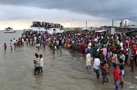 People gather on the banks of  the River Padma after a passenger ferry capsized in Munshiganj district, Bangladesh, Aug. 4, 2014.