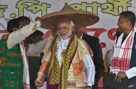 India's main opposition Bharatiya Janata Party's prime ministerial candidate Narendra Modi is presented with a traditional hat during an election campaign rally at Gogamukh, in the northeastern state of Assam, India, Monday, March 31, 2014.