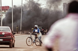 Smoke rises as Burkina Faso troops, in rear, clear debris from a road as people protest in the area against the recent coup in the city of Ouagadougou, Burkina Faso, Sept. 18, 2015.