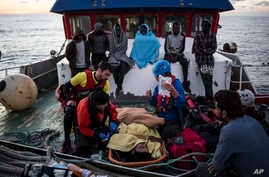 A migrant is prepared to be evacuated for medical reasons by helicopter from the Nuestra Madre de Loreto Spanish fishing vessel carrying 12 migrants rescued off the coast of Lybia, Nov. 30, 2018.