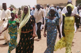 File - four female students of government secondary school Chibok, who were abducted by gunmen and reunited with their families walk in Chibok, Nigeria, April 21, 2014.