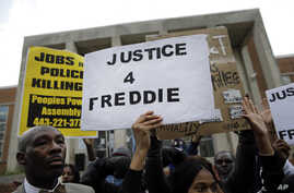 FILE - Protestors stand outside of the Baltimore Police Department's Western District police station during a march and vigil for Freddie Gray, April 21, 2015