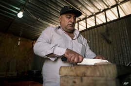 Bahaa Fransaw, cuts kebab meat, for his food stall, in Hamdaniya, Iraq, March 29, 2017.
