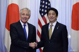 U.S. Defense Secretary Chuck Hagel (L) and Japan's Prime Minister Shinzo Abe shake hands before their meeting at the latter's former official residence in Tokyo, April 5, 2014.
