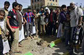 Yemenis gather at the site of a bomb explosion that targeted an army troop vehicle on its way to man a checkpoint on a street leading to two western embassies, May 9, 2014, in Sana'a.
