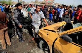 Security forces and citizens inspect the scene after a suicide car bombing hit a crowded outdoor market in Baghdad's eastern Shiite neighborhood of Sadr City, Iraq, May 17, 2016.