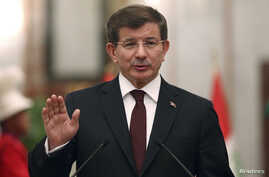 FILE - Turkey's Prime Minister Ahmet Davutoglu speaks to reporters in Baghdad, Nov. 20, 2014.