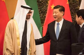 FILE - Abu Dhabi's Crown Prince and UAE Armed Forces Deputy Supreme Commander Mohammed bin Zayed Al Nayhan, left, talks with Chinese President Xi Jinping, center, during a signing ceremony at the Great Hall of the People in Beijing, Dec. 14, 2015.