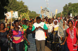 Protesters, including some holding spatulas, rally against term limit changes in Ouagadougou, Burkina Faso, Oct. 27, 2014.