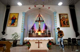FILE - A parishioner walks past the altar as members of Lower Dafei Catholic Church hold an impromptu prayer vigil as they wait for Chinese officials to arrive and cut down their church's cross in Lower Dafei Village near Wenzhou in eastern China's Z
