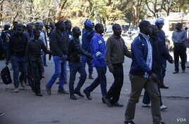 Twenty-two opposition activists facing charges of inciting violence and causing malicious damage at the ruling ZANU-PF party offices arrive at Harare Magistrates Court, Aug. 4, 2018, where they were asked to return to Monday for bail hearings. The co