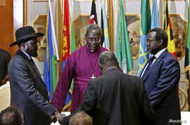 FILE - South Sudan's rebel leader Riek Machar (R) and South Sudan's President Salva Kiir (L) hold a priest's hands as they pray before signing a peace agreement in Addis Ababa, May 9, 2014.