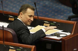 Macedonian Prime Minister Nikola Gruevski gestures, while attending a session in the parliament after resignation of two ministers from Prime Minister's cabinet and a senior state security official, on Wednesday, May, May 13, 2015, in Skopje, Macedon