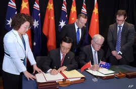 Australian Prime Minister Tony Abbott, back center, watches as China's Minister of Commerce Gao Hucheng, second left, and Australian Minister for Trade Andrew Robb, second right, sign a free trade agreement between the two countries in Canberra, Aust