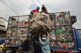 FILE - Workers load collected plastic bottles on to a truck at a junk shop in Manila, March 10, 2015. The Philippines placed third among the list of countries with the most ocean plastic pollution per year.