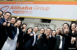 "Alibaba Group Holding Ltd founder Jack Ma (2nd L) poses as he arrives at the New York Stock Exchange for his company's initial public offering (IPO) under the ticker ""BABA"" in New York, Sept. 19, 2014."