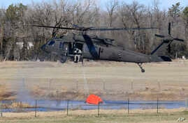 A National Guard helicopter picks up water from a small pond near Hutchinson, Kansas, March 7, 2017. Wild fires raged in parts of Kansas, Oklahoma, Texas and Colorado.