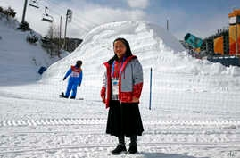 In this Feb. 12, 2018 photo, Sungsook Kim, a Catholic nun who goes by her religious name, Sister Droste, poses for a photograph at Phoenix Snow Park during the 2018 Winter Olympics in Pyeongchang, South Korea. Droste runs several centers spread acros