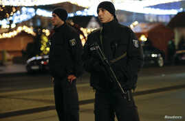 German police officers secure the site of an accident with machine guns at a Christmas market on Breitscheidplatz square near the fashionable Kurfuerstendamm avenue in the west of Berlin, Germany, Dec. 19, 2016.