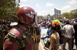 A riot policeman stands guard as opposition party supporters shout slogans , as they march in Nairobi, Oct.9, 2017.