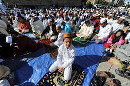 Muslim devotees take part in a special morning prayer to start their Eid al-Fitr festival, which marks the end of Muslim's holy fasting month of Ramadan, outside the Baitul Ma'Mur Mosque in Brooklyn, New York, 20 Sep 2009