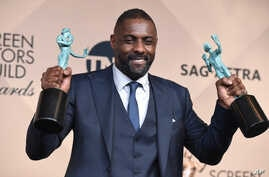 """Idris Elba poses in the press room with the award for outstanding male actor in a supporting role for """"Beasts of No Nation"""" and the award for outstanding male actor in a TV movie or miniseries for """"Luther"""" at the 22nd annual Screen Actors Gui..."""