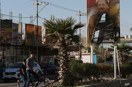 A burned poster of Massoud Barzani, the President of Iraq's autonomous Kurdish region, is displayed in front of the abandoned building of Kurdish security forces in Kirkuk, Iraq, Oct. 19, 2017.
