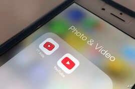 The YouTube app and YouTube Kids app are displayed on an iPhone in New York, April 25, 2018. YouTube is overhauling its kid-focused video app to give parents the option of letting humans, not computer algorithms, select what shows their children can