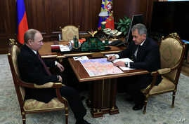 Russian President Vladimir Putin, left, listens to Defense Minister Sergei Shoigu during a meeting in the Kremlin, in Moscow, Russia, Friday, Dec. 23, 2016.
