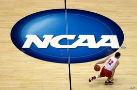 FILE - Wisconsin's Traevon Jackson dribbles past the NCAA logo during practice at the NCAA men's college basketball tournament in Anaheim, Calif., March 26, 2014.