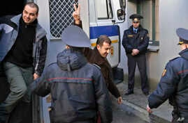 Activists, detained at a rally, are escorted by police officers as they leave a police van for a court hearing in Minsk, Belarus, March 27, 2017.