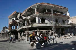 FILE - The remains of buildings line a street that was damaged the previous summer during fighting between U.S.-backed Syrian Democratic Forces fighters and Islamic State militants, in Raqqa, Syria, April 5, 2018.