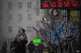 People walk past a sign advertising currency exchange rates in Moscow, Russia, Friday, Dec. 12, 2014.