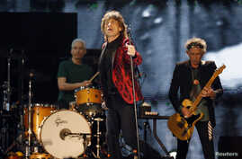 Mick Jagger (C), Charlie Watts (L) and Keith Richards of the Rolling Stones perform during a concert in Abu Dhabi, Feb. 21, 2014.