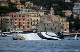 Boats are washed ashore, a day after a storm, in Rapallo, northern Italy, Oct. 30, 2018.