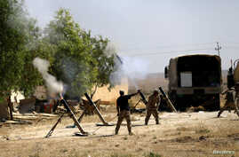Members of Iraqi Army fire mortar shells during the war between Iraqi army and Shi'ite Popular Mobilization