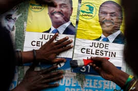 People put up campaign posters promoting presidential candidate Jude Celestin in Petionville, Haiti, Nov. 18, 2016.