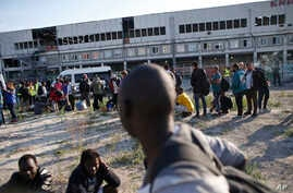 Migrants line up as they wait to be evacuated from a makeshift street camp, in Paris, France, July 7, 2017.