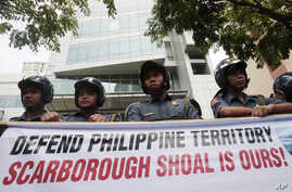 Policemen stand guard behind protesters' streamer outside the Chinese consulate in Manila's financial district of Makati, Philippines, May 11, 2012.