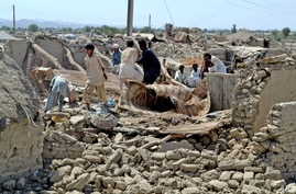 Pakistani villagers look for belongings amid the rubble of their destroyed homes following an earthquake in the remote district of Awaran, Baluchistan province, Pakistan, Wednesday, Sept. 25, 2013. Rescuers struggled Wednesday to help thousands of pe