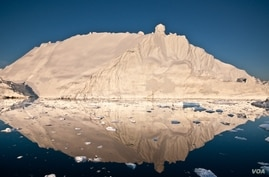 The midnight sun casts a golden glow on an iceberg and its reflection in Disko Bay, Greenland. Much of Greenland's annual mass loss occurs through calving of icebergs such as this.[Image courtesy of Ian Joughin]