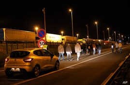 A car of the security society of Eurotunnel follows a group of migrants, in Calais, northern France, Wednesday, July 29, 2015.