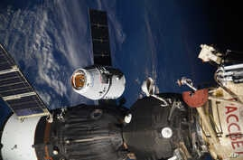 In this photo taken by Russian astronaut Sergey Ryazanskiy, the SpaceX Dragon capsule arrives at the International Space Station, Aug. 16, 2017. The capsule pulled up Wednesday following a two-day flight from Cape Canaveral, Florida.