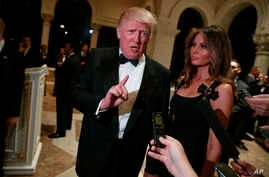 President-elect Donald Trump, with his wife, Melania, talks to reporters during a New Year's Eve party at Mar-a-Lago, Dec. 31, 2016, in Palm Beach, Fla.