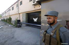 An Afghan policeman guards the gate of a guesthouse after an attack the previous night in which 14 civilians were killed, in Kabul, May 14, 2015.