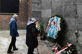 Former prisoners place candles and flowers at the Death Wall marking the 74th anniversary of the liberation of KL Auschwitz-Birkenau, in Oswiecim, Poland, Jan. 27, 2019.